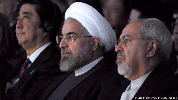 Iranian President Hassan Rouhani (C) sits next to Japanese Prime Minister Shinzo Abe (L) and Iranian Foreign Minister Mohammad Javad Zarif