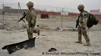 Two US soldiers with machine guns walk in fornt of a fence (Foto: Noorullah Shirzada/AFP/Getty Images)