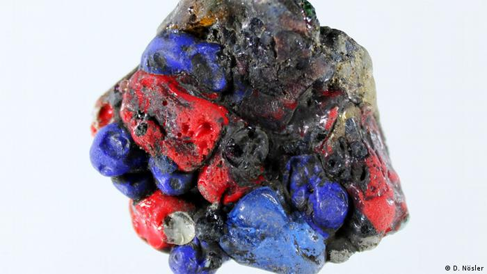 A charred and melted clump of multi-colored glass