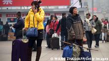 An elderly woman (R) looks on with her baggage as she prepares to take a train at a railway station in Beijing on January 23, 2014. The world's largest annual migration began on January 16 in China with tens of thousands in the capital boarding trains to journey home for Lunar New Year celebrations. AFP PHOTO / WANG ZHAO (Photo credit should read WANG ZHAO/AFP/Getty Images)