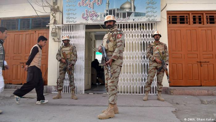 Security forces stand guard at a Shiite place of worship in Balochistan