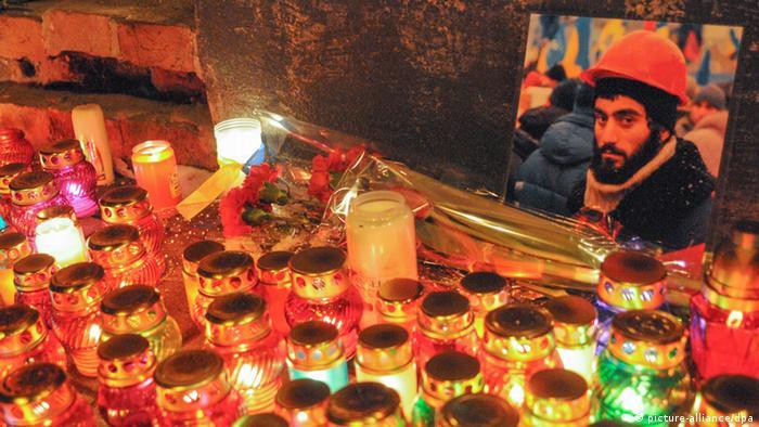 Зажженные свечи перед фото Сергея Нигояна