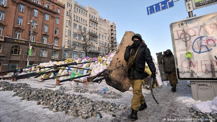 A Ukrainian protestor walks past a makeshift barricade in a city setting.
