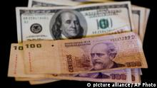 U.S. dollar bills and Argentine pesos are displayed for the photographer on a table at a currency exchange business in Buenos Aires, Argentina, Thursday, Jan. 23, 2014. Argentina's peso has plunged just over 17 percent in the last two days against the U.S. dollar, and economic analysts expect inflation to hit 30 percent this year. (AP Photo/Victor R. Caivano)