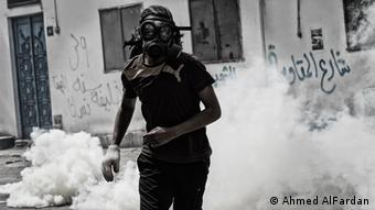 A man wearing a gas mask stands among a cloud of tear gas