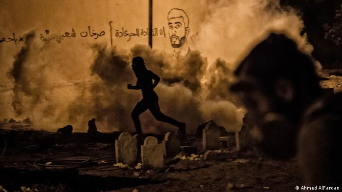 A man runs through a cloud of tear gas smoke