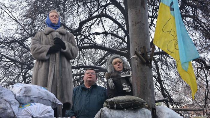 A Ukrainian woman stands at one barricade, with two individuals standing near her (c) DW/R. Goncharenko