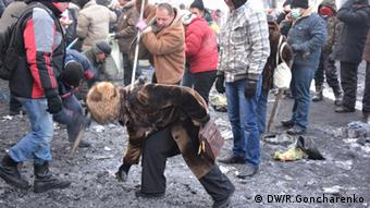 A woman picks up ice surrounded by other protesters (C) DW/R. Goncharenko