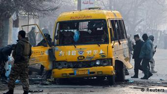 Afghan policemen inspect the wreckage of a bus hit by a suicide attack in Kabul January 26, 2014.