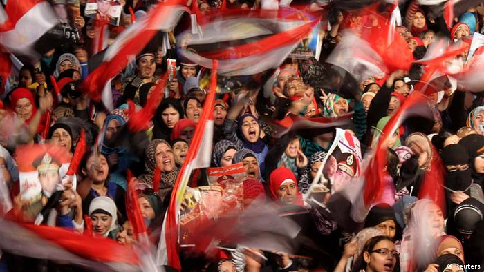 Protesters in Cairo waving flags on Cairo's Tahrir Square