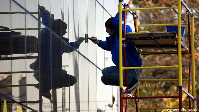A man cleans windows at the site of the Sochi Games