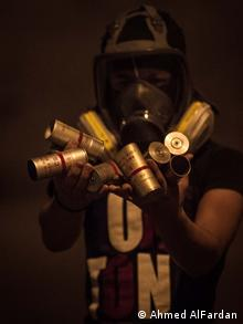 A protester holds up a collection of empty tear gas canisters with the red stripe