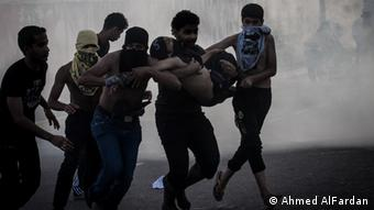 A group of young men carry away an injured protester