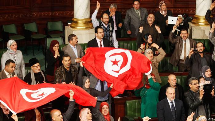Tunesische Parlamentsabgeordnete schwenken nach der Verabcsheidung der neuen Verfassung die Landesfahne. Foto: REUTERS