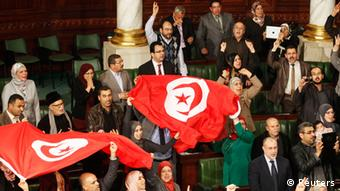 Members of the Tunisian parliament wave flags after approving the country's new constitution