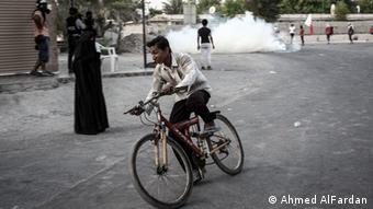 A young man on a bike speeds away from a tear gas attack