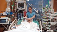 In der Anästhesiologie-Intensivstation der Medizinischen Hochschule in Hannover kümmert sich Schwester Claudia um einen Patienten, der in ein künstliches Koma versetzt wurde - sie hält hier Schläuche, die zur Beatmung notwendig sind (Foto vom 07.03.2005). Um die Heilungschancen zu verbessern, werden Patienten bei schweren Erkrankungen sowie nach Unfällen oder Operationen in ein künstliches Koma versetzt. In den Behandlungsräumen der Station, die alle gleich ausgestattet sind, gibt es einen Überwachungsmonitor für den Kreislauf des Patienten (oben), eine künstliche Beatmungsmaschine mit Monitor zum Überwachen der Atmung (unten links) sowie Infusionsautomaten (Perfusoren) für Medikamente, die intravenös verabreicht werden. Foto: Wolfgang Weihs (zu dpa-Reportage: Künstliches Koma hilft Patienten zum Überleben vom 23.05.2005) +++(c) dpa - Report+++