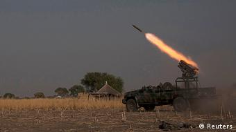 A rebel vehicle standing in the middle of a field in the vicinity of Bor fires a rocket. At some distance a car is approaches a lone dwelling. (Photo: Reuters/George Philipas )