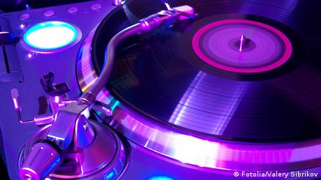 A record on a turntable - lit in purple light
