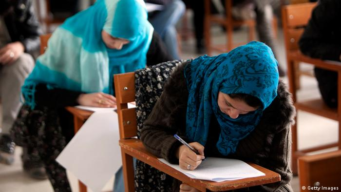 Two Afghan women wearing colorful headscarves lean over their desks while studying.