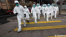 Health officers in full protective gear cross a road near a wholesale poultry market in Hong Kong January 28, 2014. Hong Kong began culling 20,000 chickens and suspended imports of fresh poultry from mainland China for 21 days on Tuesday after the discovery of the H7N9 bird flu virus in a batch of live chicken from the southern province of Guangdong. REUTERS/Tyrone Siu (CHINA - Tags: HEALTH ENVIRONMENT SCIENCE TECHNOLOGY ANIMALS)
