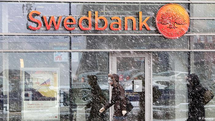 People walk past a Swedbank branch in Riga
