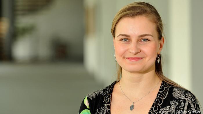 Deutschlernerin Irina aus Russland (lange, blonde Haare, Ohrringe, eine Kette um den Hals und ein gemustertes schwarzes Kleid) lächelt in die Kamera