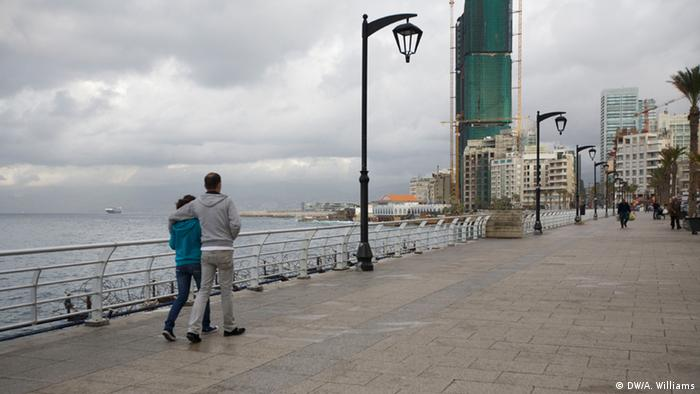A couple stroll along a beach promenade in Beirut