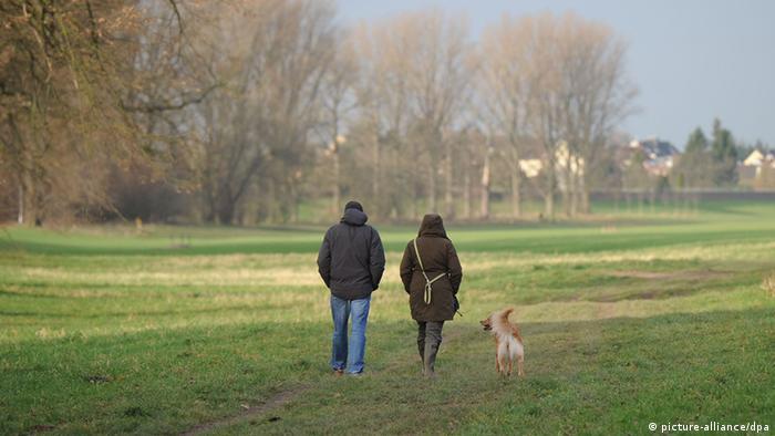 Ein Mann und eine Frau gehen mit Hund spazieren