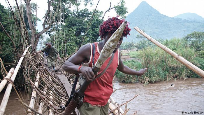 Milizionär geht über brüchige Bambus-Brücke (Foto: Alexis Bouvy)