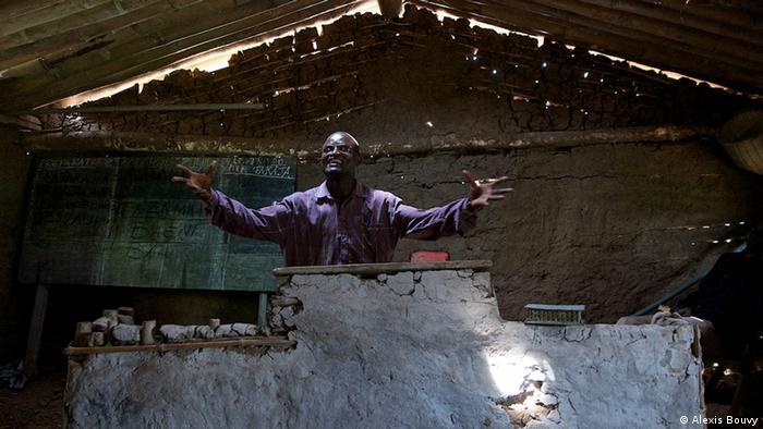 Pfarrer steht in brüchiger Hütte und breitet die Arme aus (Foto: Alexis Bouvy)