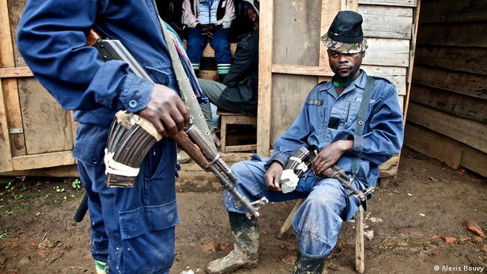 Milizionäre in Polizeiuniform sitzen vor Hütte (Foto: Alexis Bouvy)