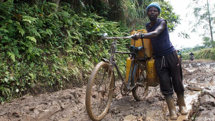 Ein Banenbauer schiebt sein Fahrrad durch den Schlamm (Foto: Alexis Bouvy)