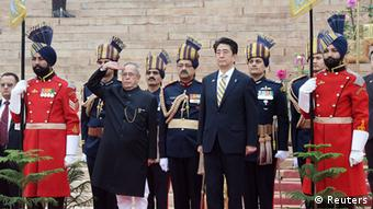 India's President Pranab Mukherjee salutes as Japan's Prime Minister Shinzo Abe (4th R) looks on before heading towards the venue for the Republic Day parade, at India's presidential palace Rashtrapati Bhavan in New Delhi January 26, 2014. Abe was the chief guest at India's Republic Day celebrations on Sunday.