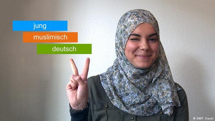 Comiczeichnerin Soufeina Hamed mit Kopftuch; ihre Hände machen das Victory-Zeichen.