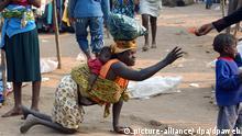 Eine gehbehinderte Mutter mit Baby auf dem Rücken greift am 20.07.2005 in den Slums von Roque Santeiro in Angolas Hauptstadt Luanda, in denen über 300 000 Menschen unter unwürdigsten Verhältnissen leben, nach einem für sie bestimmten 10 Kwanza-Geldschein (umgerechntet 10 Cent). Foto: Wolfgang Langenstrassen +++(c) dpa - Report+++