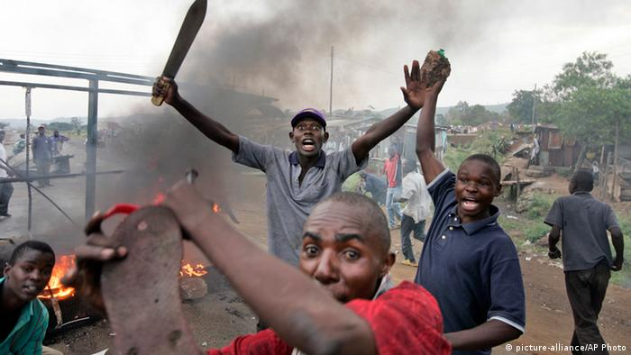 Picture showing Kenyan rioters branding a matchete and raising stones as fire burns in the background during the 2007 post election violence