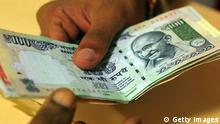 A customer deposits Indian rupee currency notes at a bank in Mumbai on September 3, 2013. India's currency slid sharply and the share market crashed nearly 3.5 percent in another major sell-off caused by uncertainty in the Middle East and a new gloomy economic forecast by Goldman Sachs. The rupee, the worst performing major currency in Asia this year, skidded 3.25 percent to 68.15 to the dollar as shares closed down 651 points or 3.45 percent to 18,234.66 points. AFP PHOTO/Indranil MUKHERJEE (Photo credit should read INDRANIL MUKHERJEE/AFP/Getty Images)