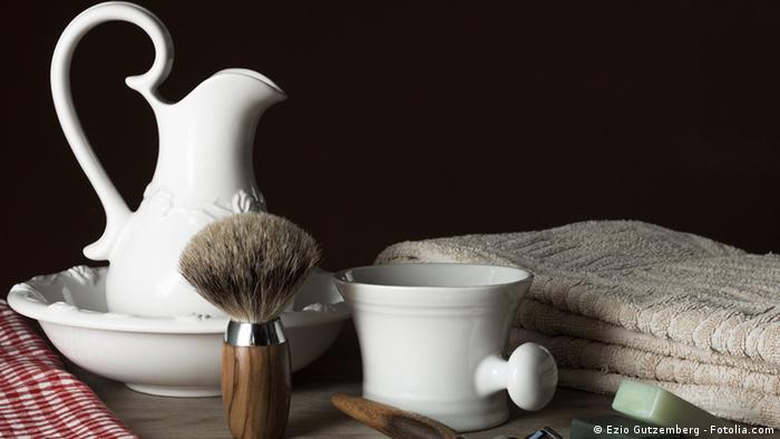Verschiedene klassische Rasurutensilien, wie Rasierpinsel, Seife, Wasserkanne und Handtuch, stehen vor schwarzem Hintergrund
