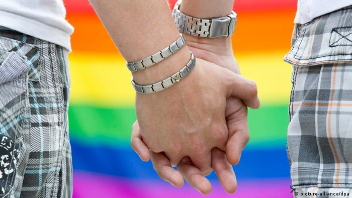 two men holding hands, gay pride flag