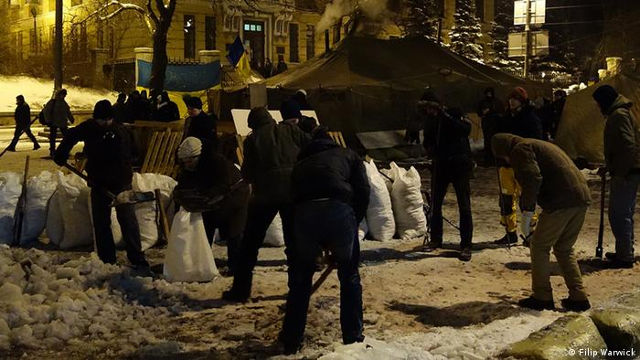 Dark photo taken at night of protesters on Independence Square in Ukraine who are packing bags full of snow and ice, which will be used as part of a barricade Photo: Filip Warwick