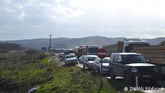 A queue of waiting semi trailers stretches into the distance after protesting villagers block a regional highway