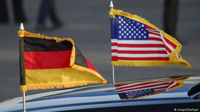 A German flag flies next to an American one on the hood of a new automobile.