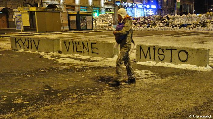 Dark photo taken at night of a security volunteer walking past a barricade spayed with the words 'Kiev - Free City' Photo: Filip Warwick