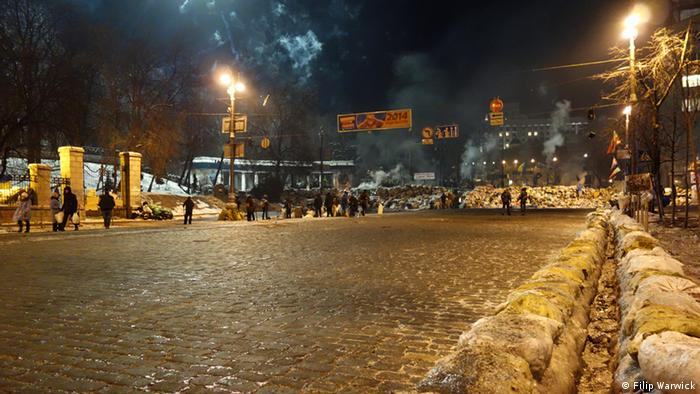Dark photo taken at night of protesters on Independence Square in Ukraine with a close-up of the gutters that have been dug out of the snow Photo: Filip Warwick