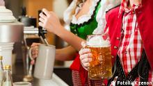 #51703901 - Junge Frau in Tracht zapft ein Bier im Restaurant © Kzenon