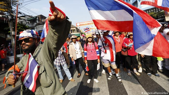 hai anti-government protesters wave Thai national flags as they march along a main road of Chinatown during their 'Bangkok Shutdown' rally in Bangkok, Thailand, 01 February 2014.