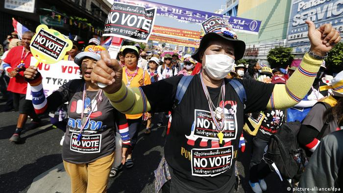 Thai anti-government protesters hold 'No Vote' placard as they march along a main road in Chinatown during the Bangkok Shutdown rally in Bangkok, Thailand, 01 February 2014.