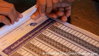 A Thai Muslim villager places his thumb pm a ballot paper prior to casting his vote at a polling station in Narathiwat province on February 2, 2014.