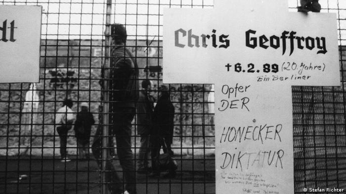 A cross of remembrance has the name Chris Gueffroy had written on it in a black-and-white photograph.